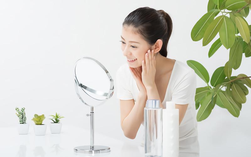 鏡で肌の調子を見る女性