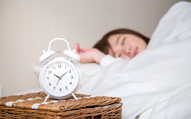 10時を過ぎる時計とベッドで眠る女性